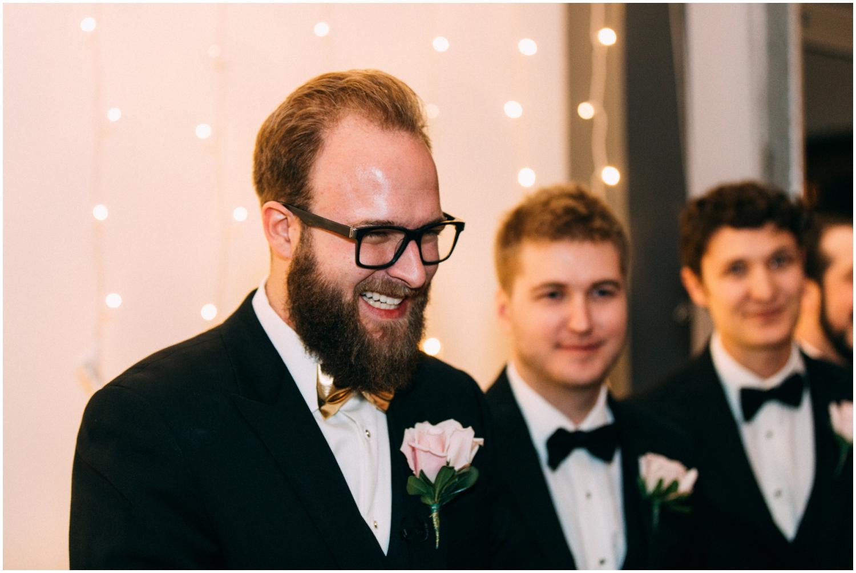 Groom watching the bride walk down the aisle