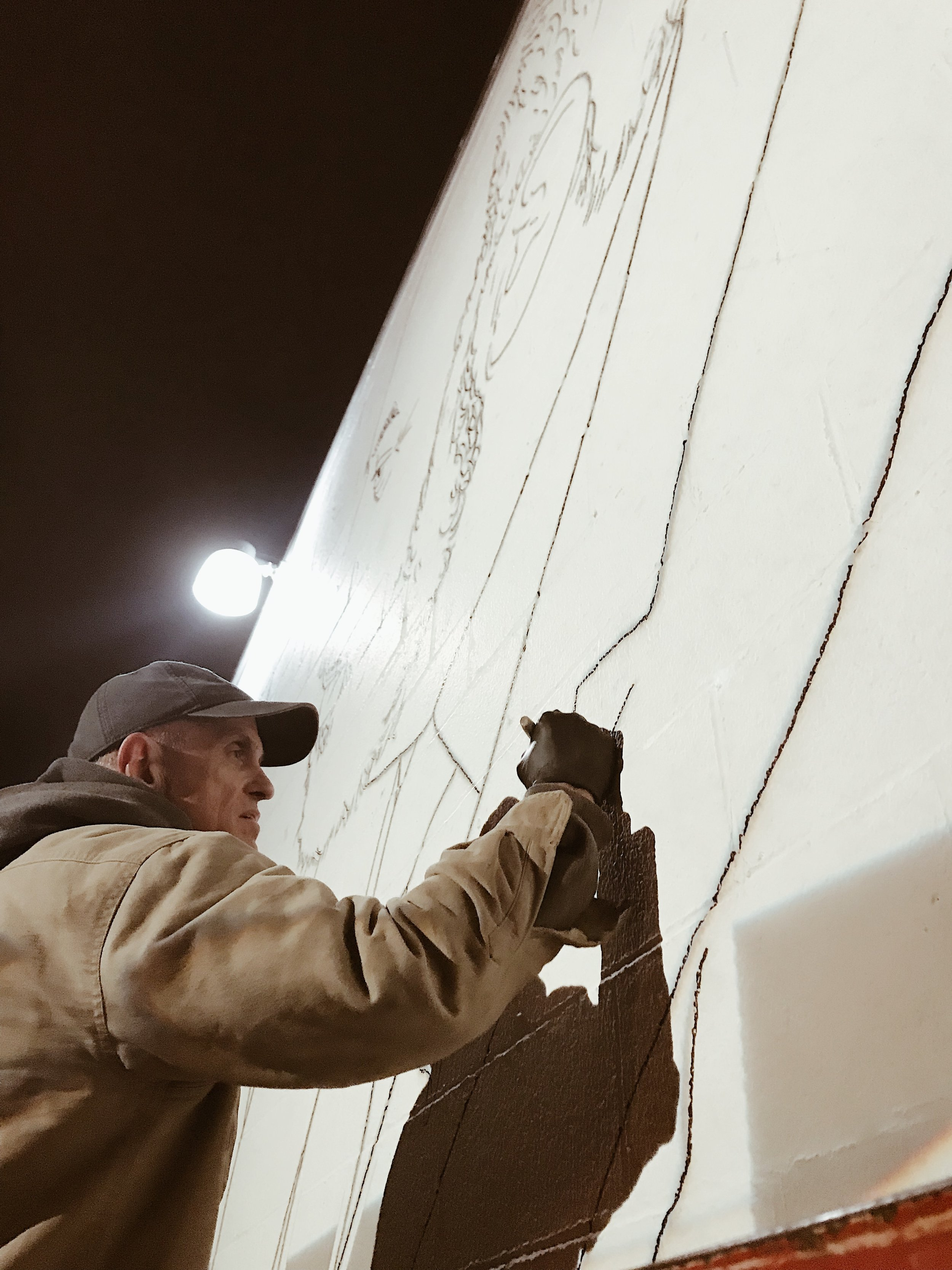 Sketching it out. - Burrrr!!! Working at night in freezing rain, we blew up the art directly on the wall.