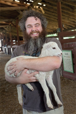 Image shows Patrick Rothfuss (A Famous Author) holding a very cute lamb.
