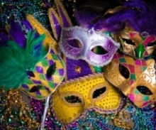 Image shows 5 Mardis Gras** masks over many strings of beads.