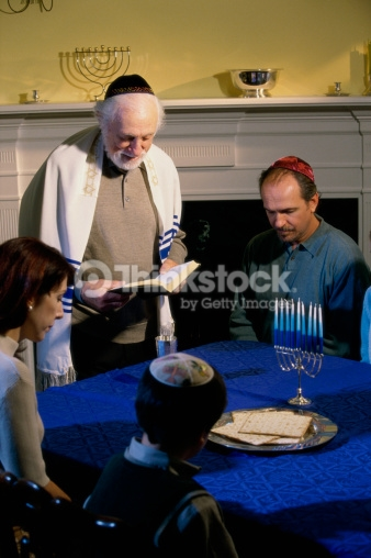 Image shows an older balding man wearing a  tallit  and holding an open  siddur  standing next to a table. To his left is a seated woman with short hair, to her right is a young boy in a sweater vest, button down shirt and Hanukkah themed suede  kippah.  To the right of the older man is a seated man in a long sleeved polo shirt with a red satin  kippah.  There is someone seated next to this man, but the image cuts off everything but some arm in a blue sleeve. On the table is a silver plate with square machine made matzah and an unlit  ḥanukkiyah  with all of the arms holding blue and white striped candles.