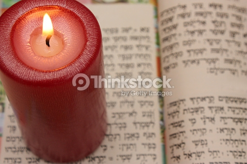 Image shows a lit red pillar candle sitting on the pages of an open Hebrew prayerbook.