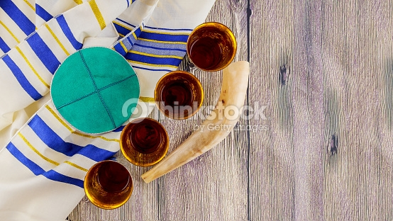 Image shows a  tallit  with blue and gold stripes on a rough wooden surface. Arranged on and beside the  tallit  from left to right are: a teal suede  kippah  with a silver border, 4 mostly empty silver  kiddush  cups in a diagonal line, and a  shofar.