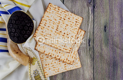 Image shows a blue and gold striped tallit (with atarah showing this time, for variety) on wooden slats. Over the tallit are (from left to right): a shofar, a black suede kippah with a gold border embossed with Jewish stars, and matzah. Once again, juxtaposition fail.