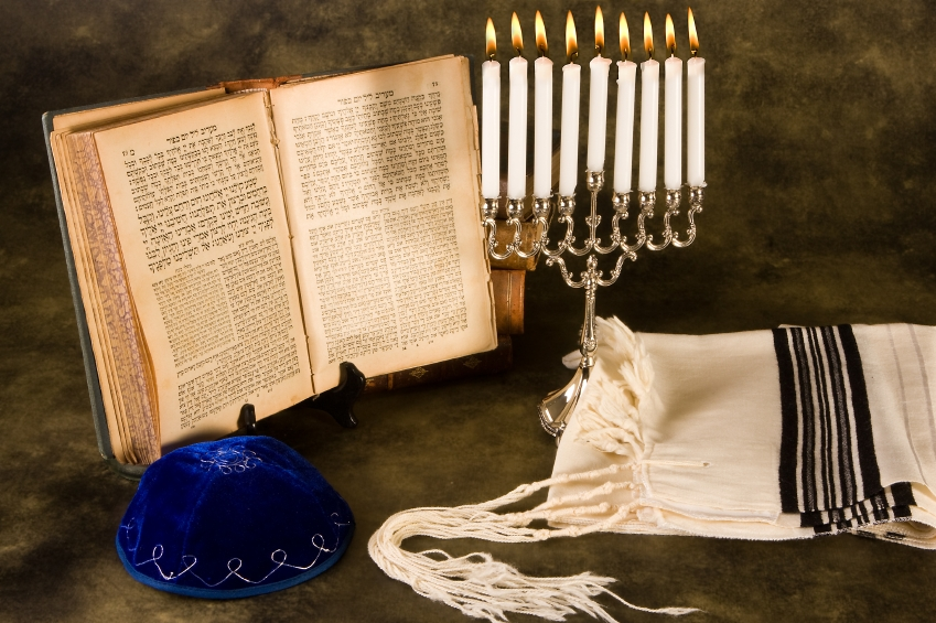 Image shows an open Hebrew prayerbook on a stand, a blue velvet  kippah  with silver embroidery, a  ḥanukkiyah  with all its candles lit, and a folded  tallit  with black and silver stripes.
