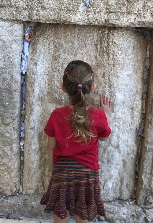 Monster at the western retaining wall of the Temple Mount (also known as The Kotel). [Image shows a small child in a red t-shirt and rainbow skirt touching the stones of a wall that's over 2000 years old.]