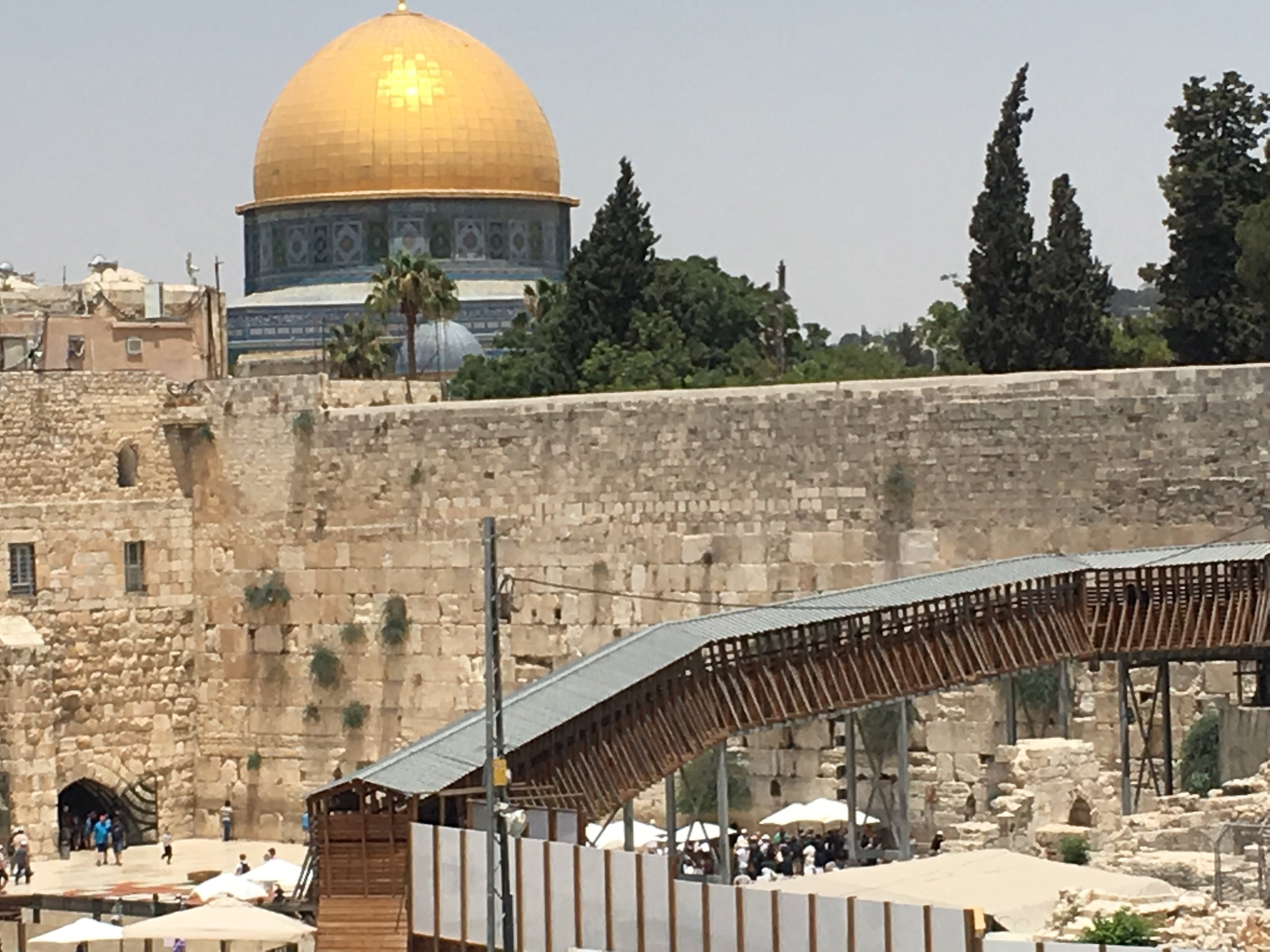Classic shot of the Kotel and Temple Mount. [Image shows the stone wall of the Temple mount and the gold dome of the Dome of the Rock mosque]