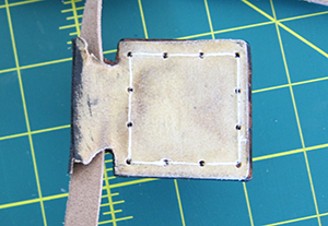 Overhead view of the upside down repaired  tefilah shel rosh. The bottom is now entirely flat, and the stitching holding the entire object together has been replaced.