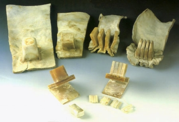 Rawhide being shaped into  tefillin .  [Image shows large sheets of ivory colored rawhide with vague and then more precise box shaped protrusions in one end. In the front are unpainted  tefillin  boxes]