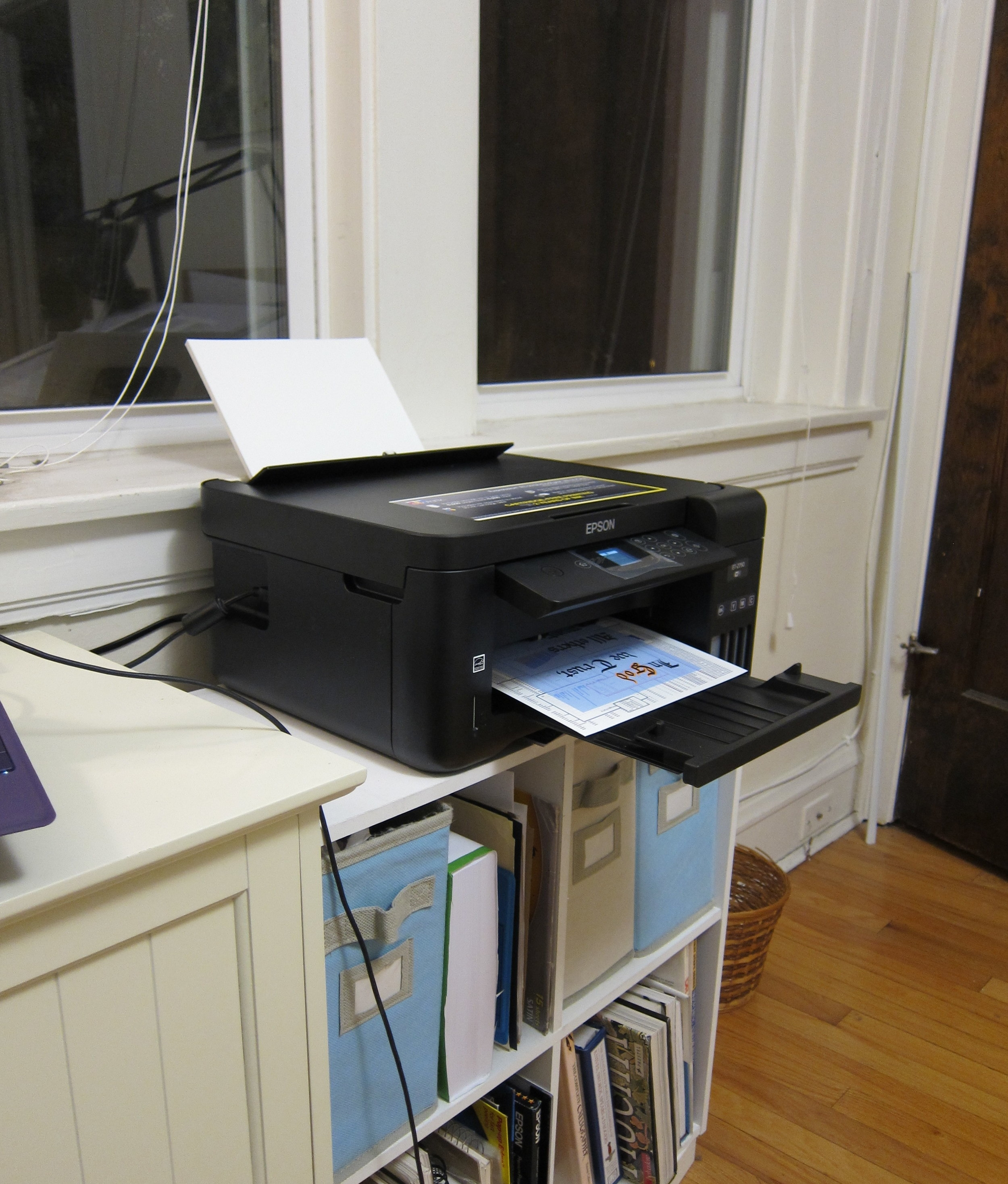 The new printer calmly doing its job.  [Image shows a printer on top of a bookshelf with a print half completed coming out of it]