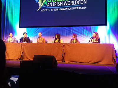 One of the three panels I attended. Seated under a large screen with the Dublin 2019 logo are moderator Mur Lafferty, Yoon Ha Lee, Becky Chambers, Cat Valente, Naomi Novik, and Mary Robinette Kowal
