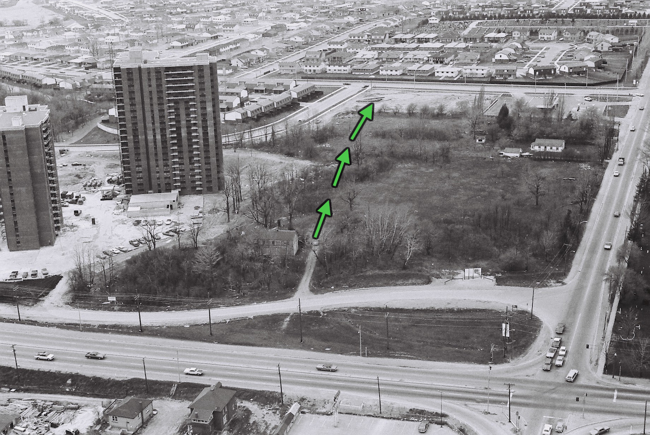 This aerial photo taken prior to the move shows the location of Cherry Hill and the 400 yards north journey through bush needed to re-locate the home to its new site. Note the sign at the bottom of the photo announcing the planned road re-alignment. The two apartment towers, a McLaughlin development, were under construction at the time. His Mississauga Valleys residential community to the north, was also nearing completion.