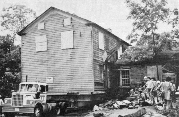 The home (without the stone foundation) sits on a flatbed truck ready for the move.
