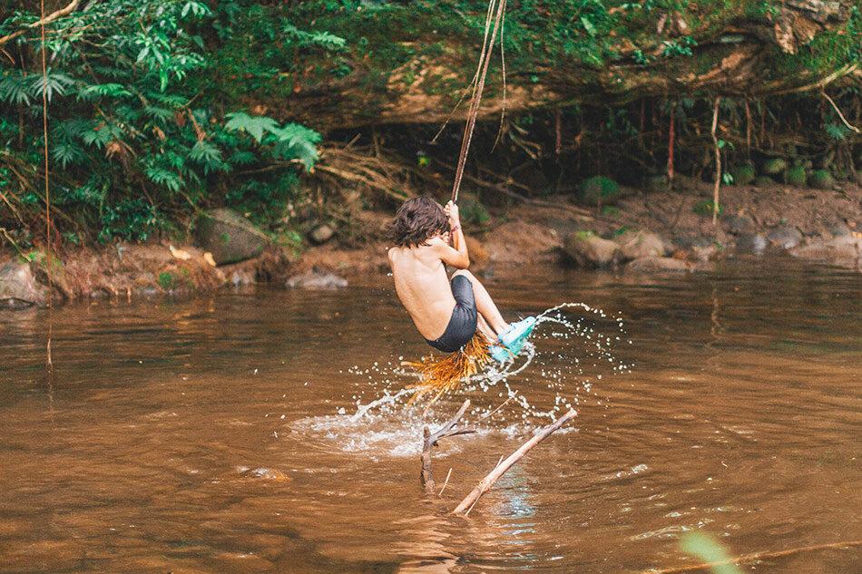 Boy hanging over water in Ecuador