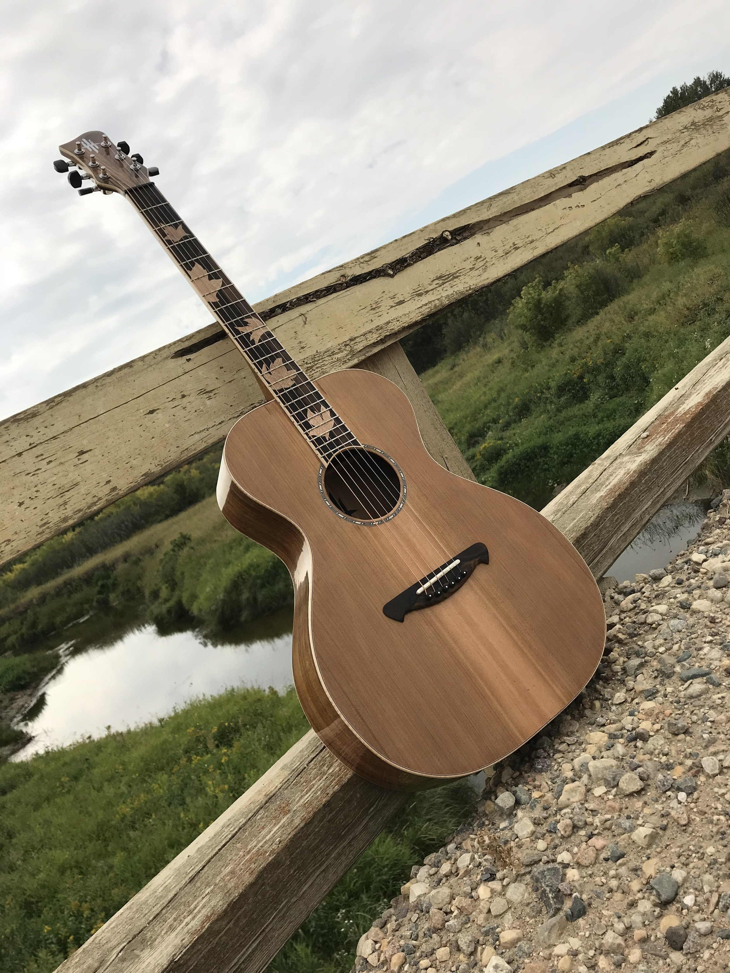 """-O Scale Acoustic Guitar  -Tazmanian Blackwood Back, Sides and Neck  -Western Red Cedar Top  -Zircoti Bridge and Fretboard with Flamed Maple Inlays  -English Walnut Head Veneer with Pearl Inlay  -Flamed Maple Bindings  -25.5"""" Scale  -Tusq Nut and Saddle"""