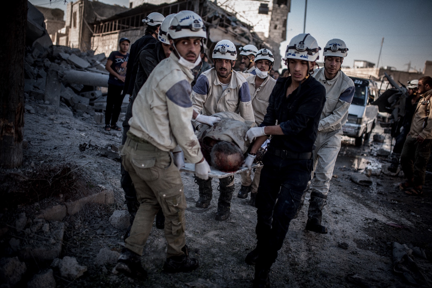 Members of the  Civil Defense Force  carry a body after a barrel bomb hit a bus