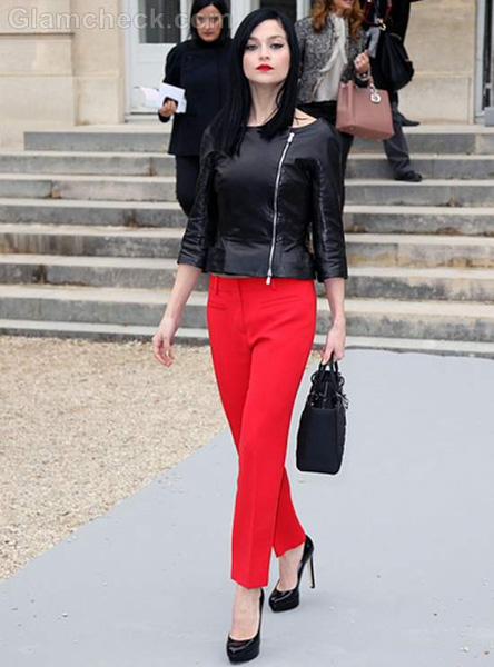 Black leather top pairs with tailored red pants and shiny black pumps