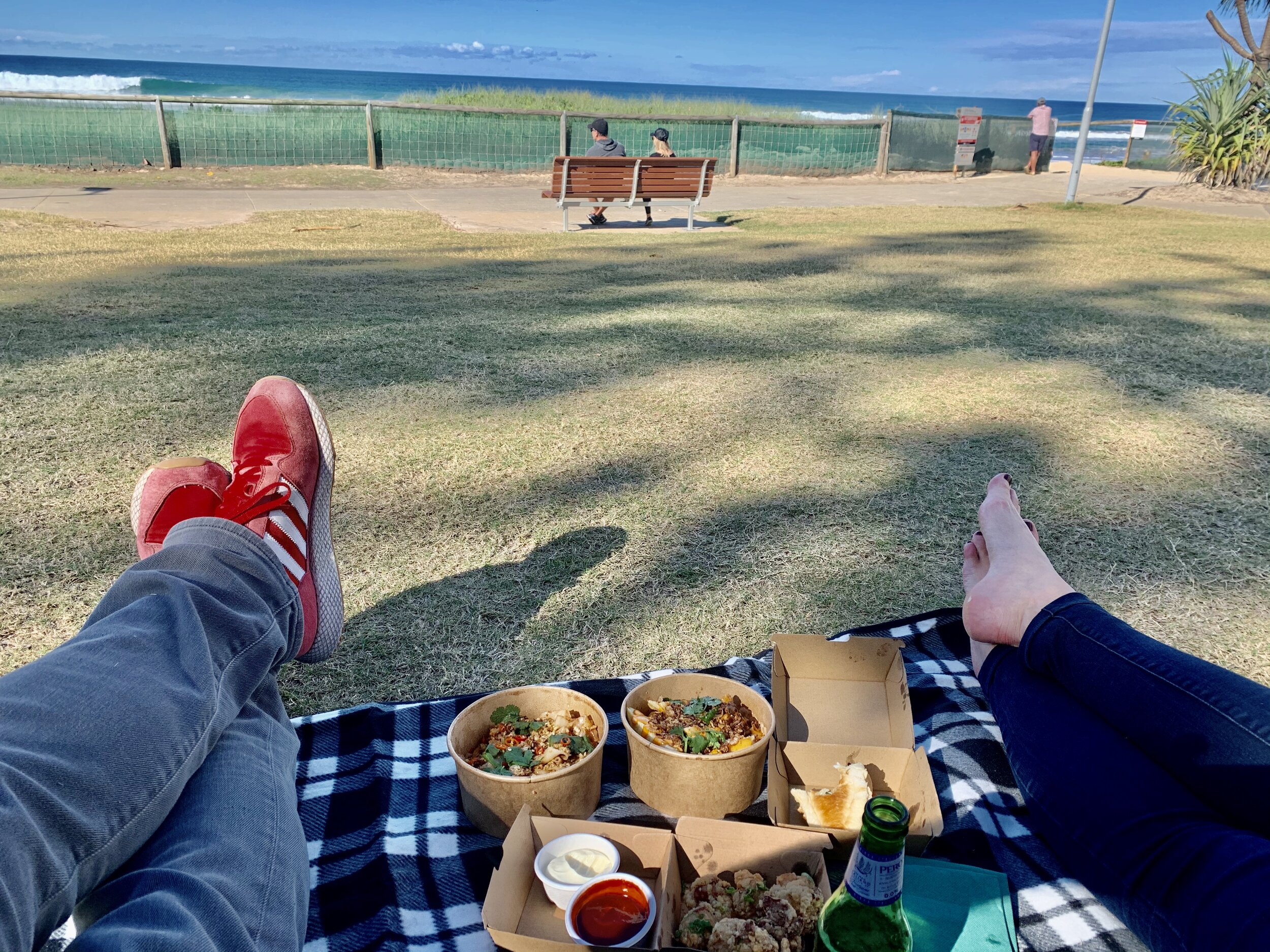Two people picnic at the beach
