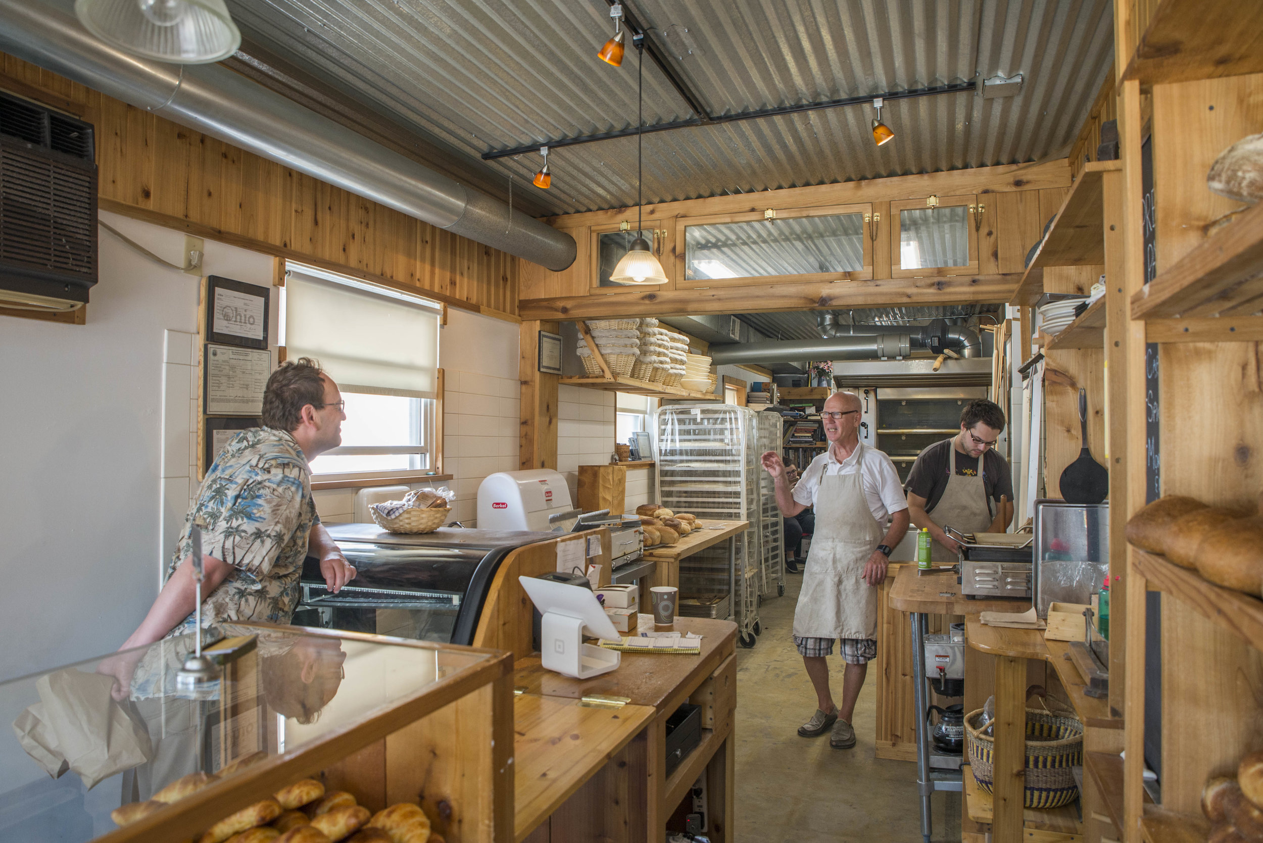 A customer talks to proprietor of Athens Bread Company, Doug Wistendahl (middle) in Athens, Ohio on September 9, 2016.