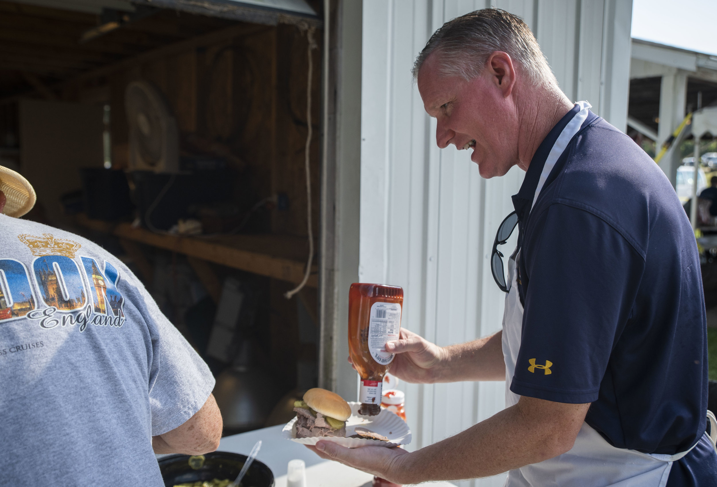 U.S. Representative, Steve Stivers (OH-15) places condiments on his sandwich while interacting with a member of the West Jefferson community.