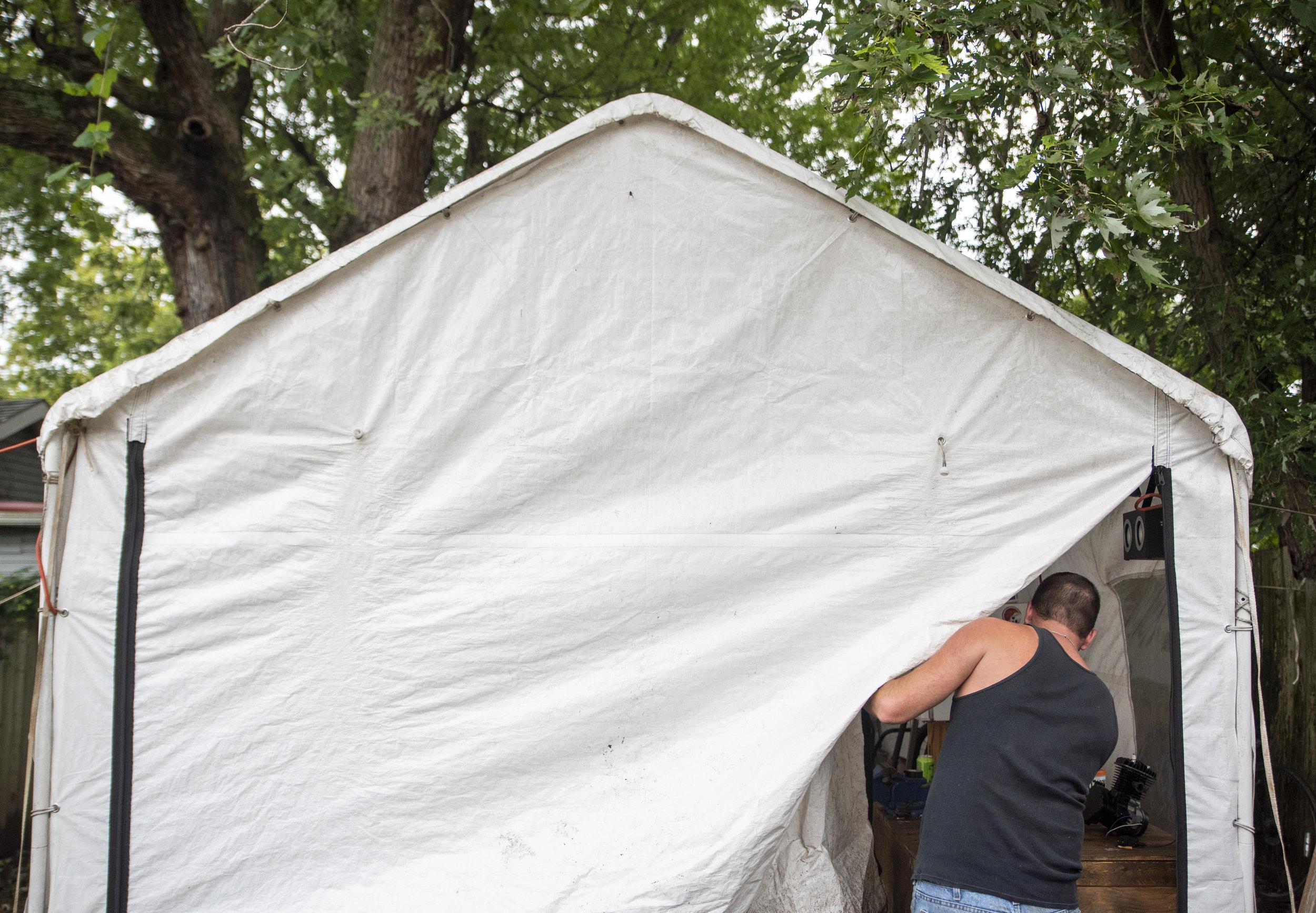 Calvin unzips the tarp to his garage of motorized vehicles.