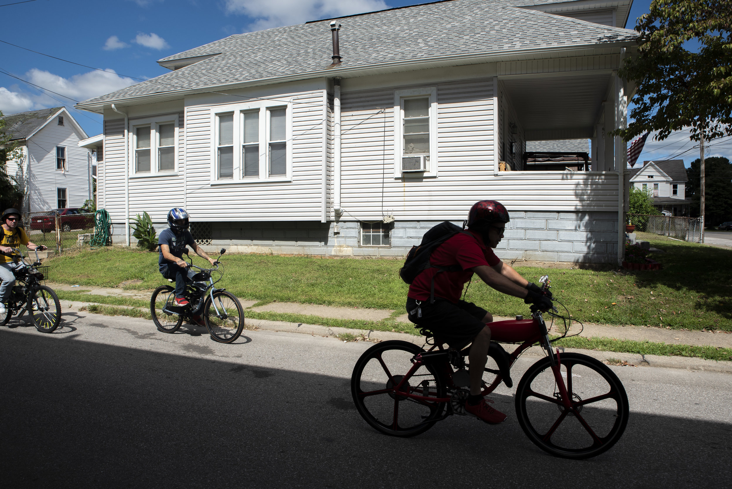 (from left to right) Steve Ramsey, Dale Akers and Rex begin to accelerate their motorized bicycles to prepare for a ride around the City of Parkersburg.