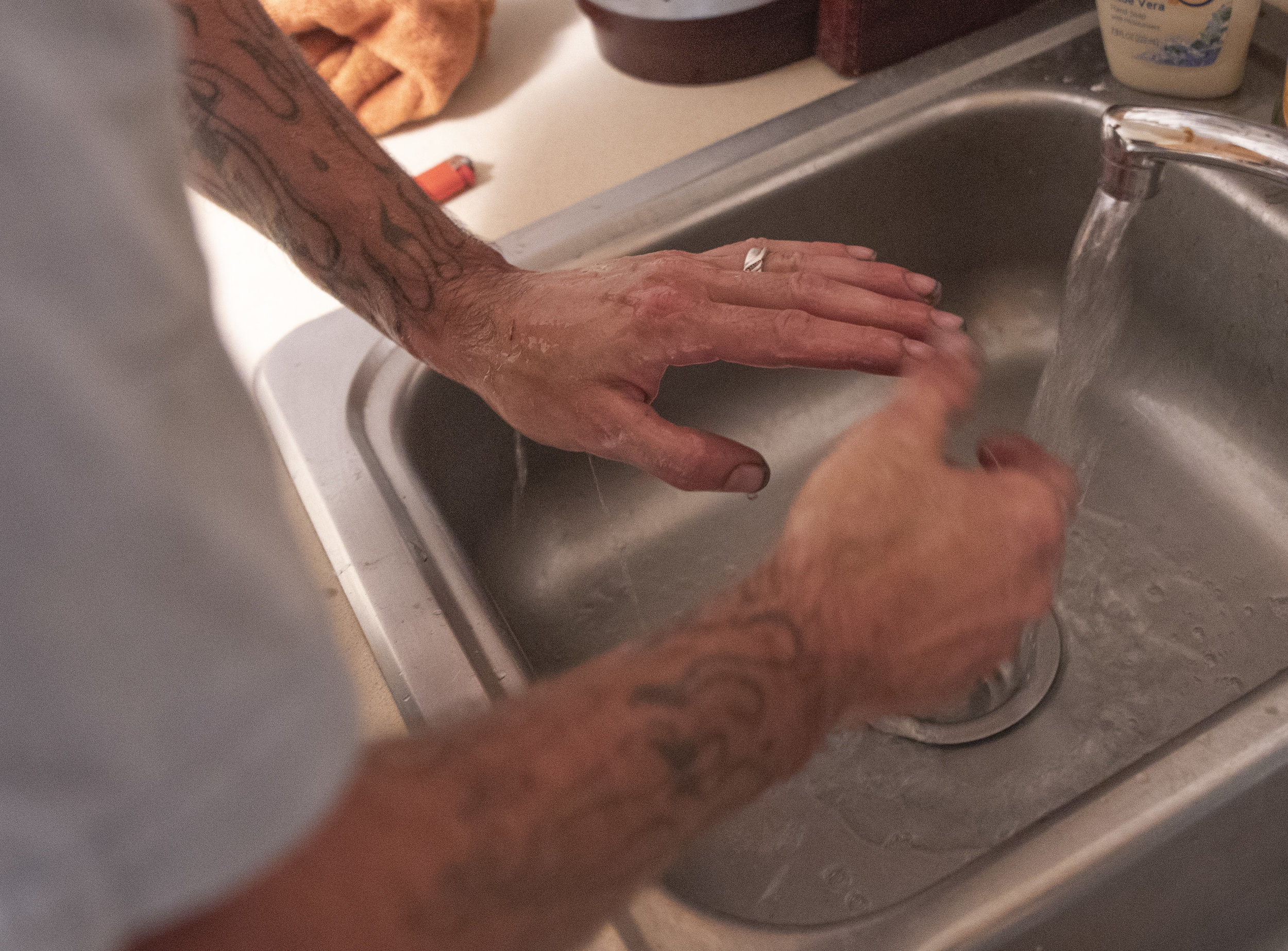 Calvin washes the grime from his hands in the sink after repairing motorized vehicles all day.