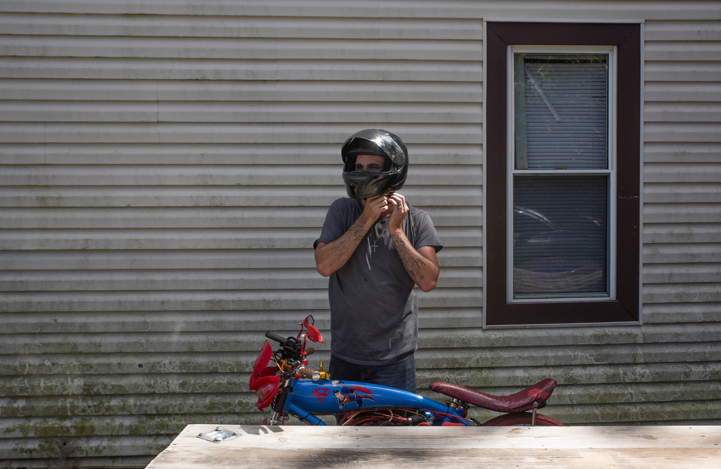 """Calvin prepares to ride his motorized bicycle, """"Superman"""", as he tightens the straps on his helmet."""