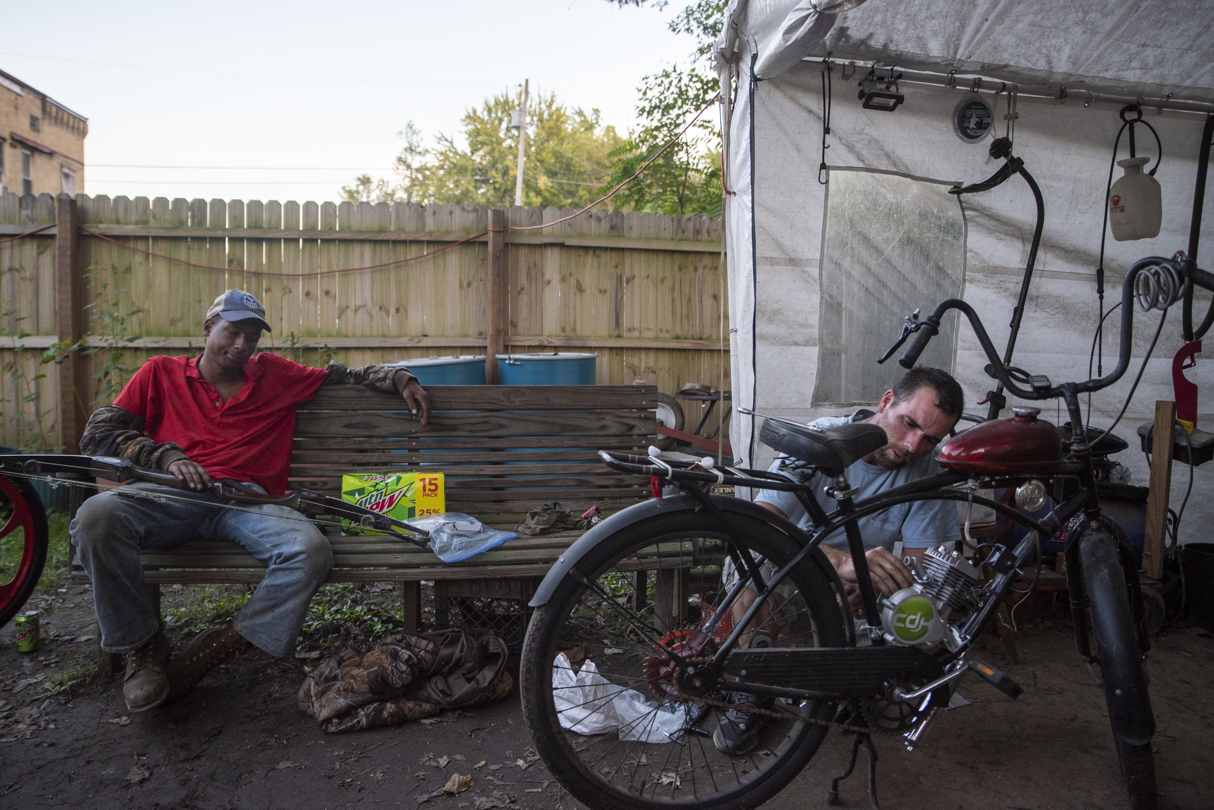 Calvin and an unnamed gentleman converse while Calvin works on repairing a motorized bicycle.