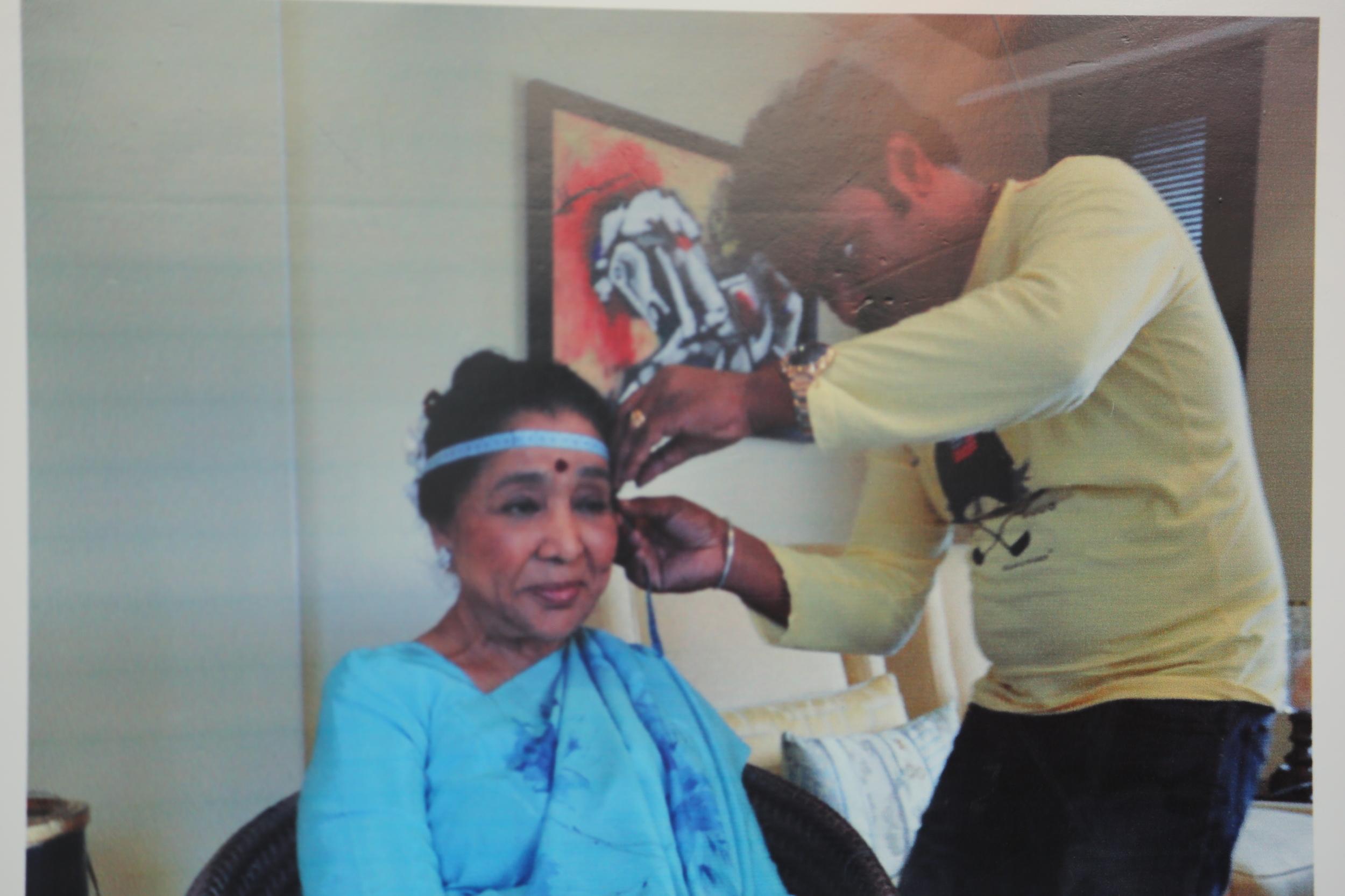 Photo of a photo: Kandalloor measuring Asha Bhosle's head for a wax statute.
