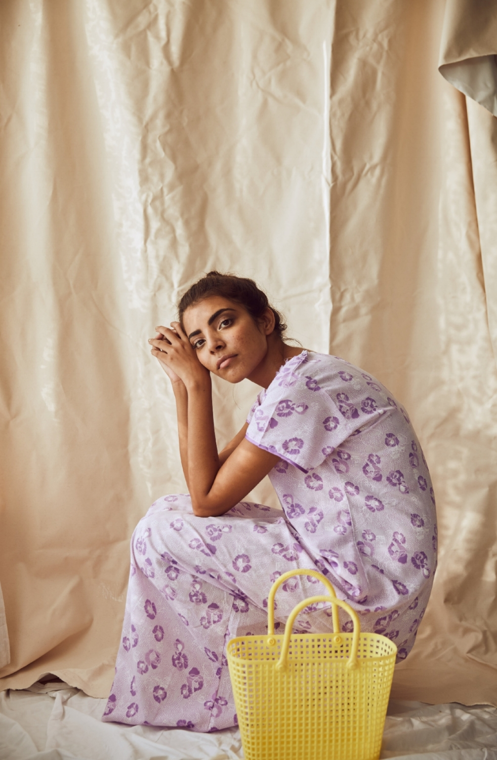 The model wears a soft mauve nightie with a delicately sprinkled tulip pattern and mother-of-pearl buttons, accessorized with a lemon yellow plastic lunch basket.