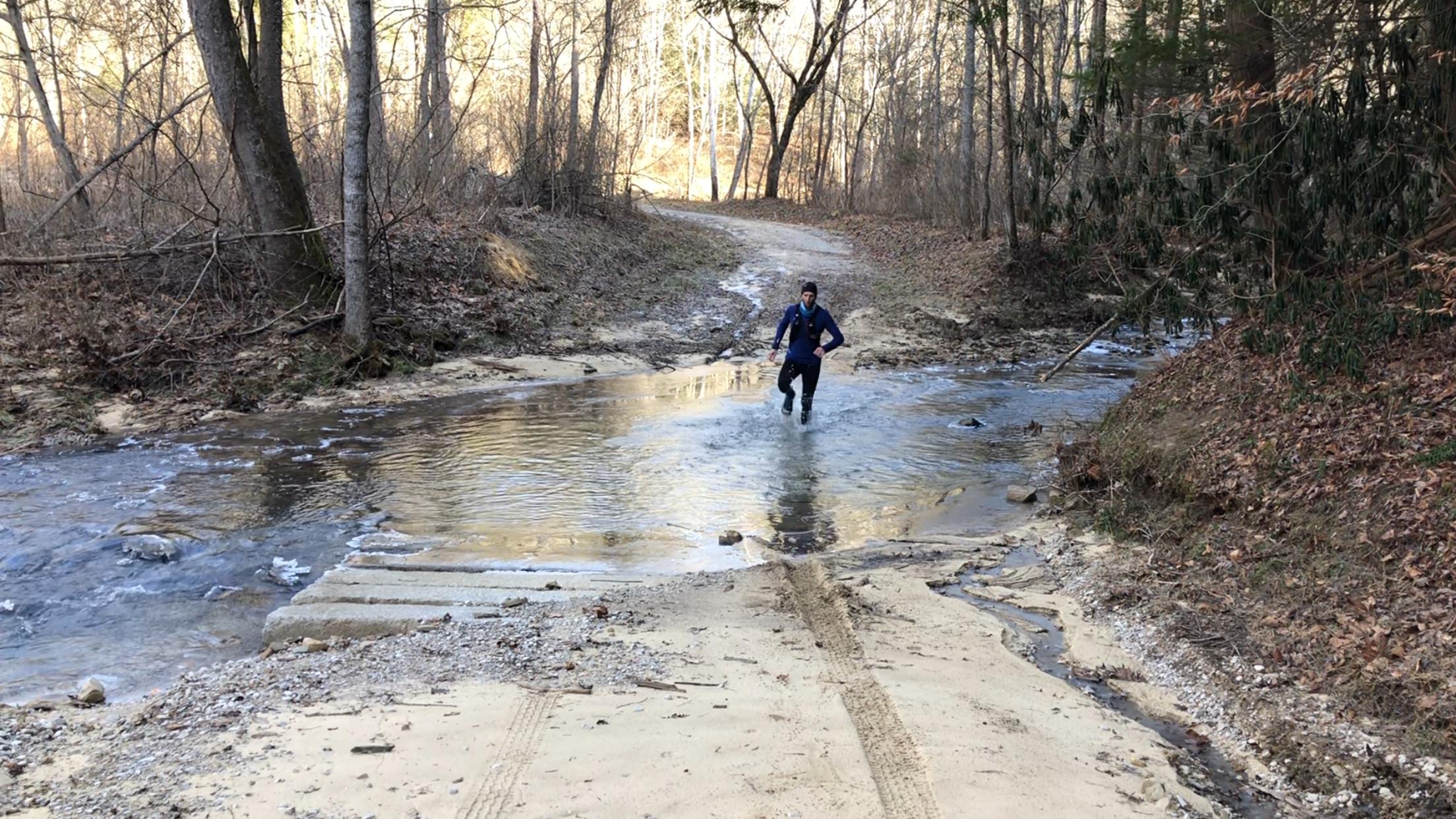 A freezing runner crosses Raccoon Creek on a winter training run.