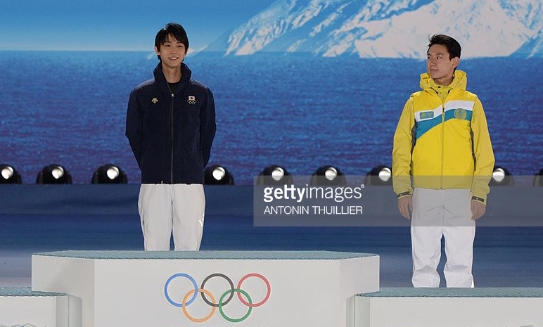 Denis Ten, the bronze medalist, looks at champion Yuzuru Hanyu during medal ceremony at the 2014 Winter Olympics.