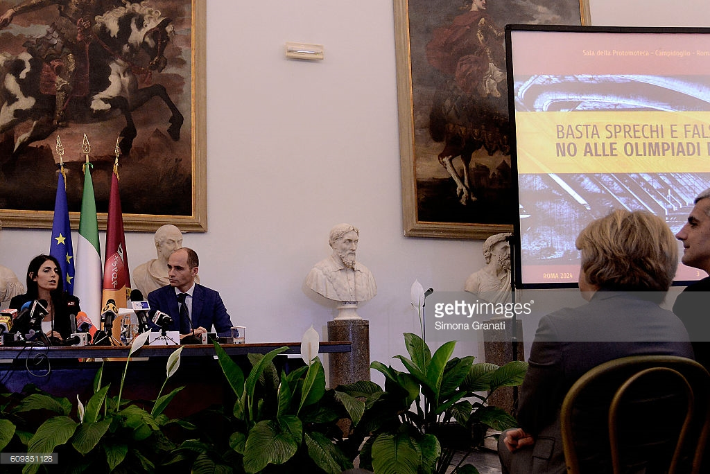 """Rome mayor Virginia Raggi (far left)officially rejecting the city's 2024 Olympic bid, with the sign saying, """"Enough waste...no to the Olympics."""""""