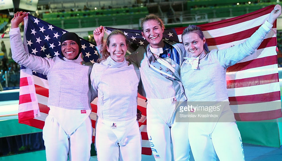 Ibtihaj Muhammad, Mariel Zagunis, Monica Aksamit, and Dagmara Wozniak after winning the team sabre bronze medal at the 2016 Summer Olympics. Muhammad was the first U.S. athlete ever to compete in hijab at the Olympics.