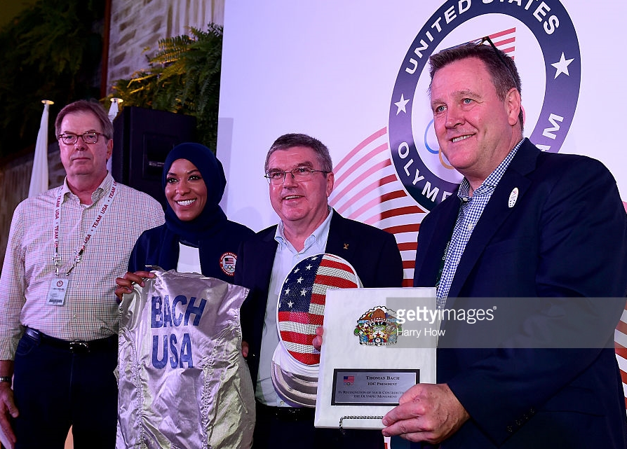 Muslim-American Olympic fencer Ibtihaj Muhammad joined, from left, USOC chairman Larry Probst, IOC President Thomas Bach and USOC chief executive Scott Blackmun in a gift presentation to Bach at the Rio Olympics.  Muhammad's presence now looks like window dressing in the light of the USOC's anodyne statement about president Trump's Muslim-targeted immigration and travel ban.