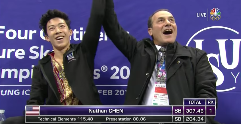 Like a referee in a boxing ring, coach Rafael Arutunian raises Nathan Chen's arm to signify the sport's new champion heavyweight.