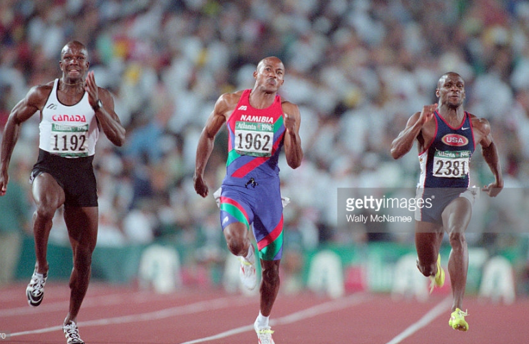 Namibia's Frankie Fredericks (center) finishing second to Canada's Donovan Bailey (left) in the 100 meters at the 1996 Olympics.  U.S. runner Dennis Mitchell (right) was fourth.