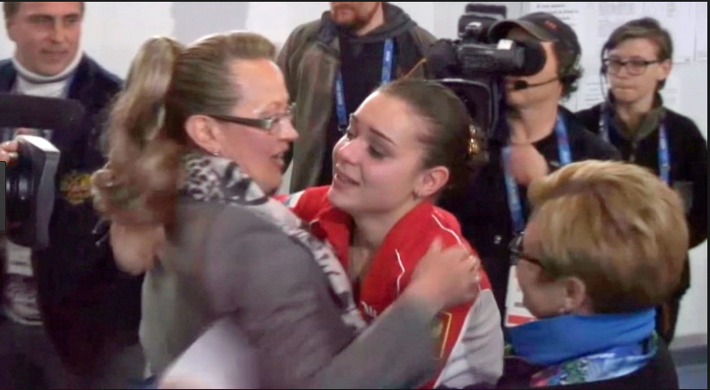 Russian judge Alla Shekhovtseva hugging compatriot Adelina Sotnikova after Shekhovtseva was on the judging panel that chose Sotnikova as 2014 Olympic champion.  (Screenshot from Olympic telecast.)