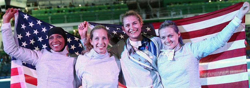 Ibtihaj Muhammad, Mariel Zagunis, Monica Aksamit, and Dagmara Wozniak (L-R) celebrate wit Old Glory after winning a bronze medal in team saber at the 2016 Olympics. (Getty Images)