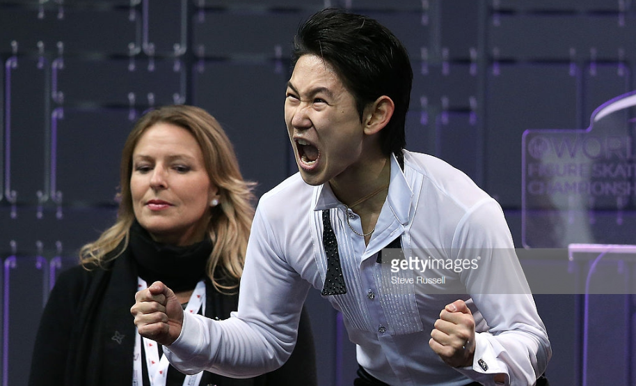 "With his choreographer, Lori Nichol, in the background, Denis Ten exults over his performance as ""The Artist"" at the 2013 World Figure Skating Championships."