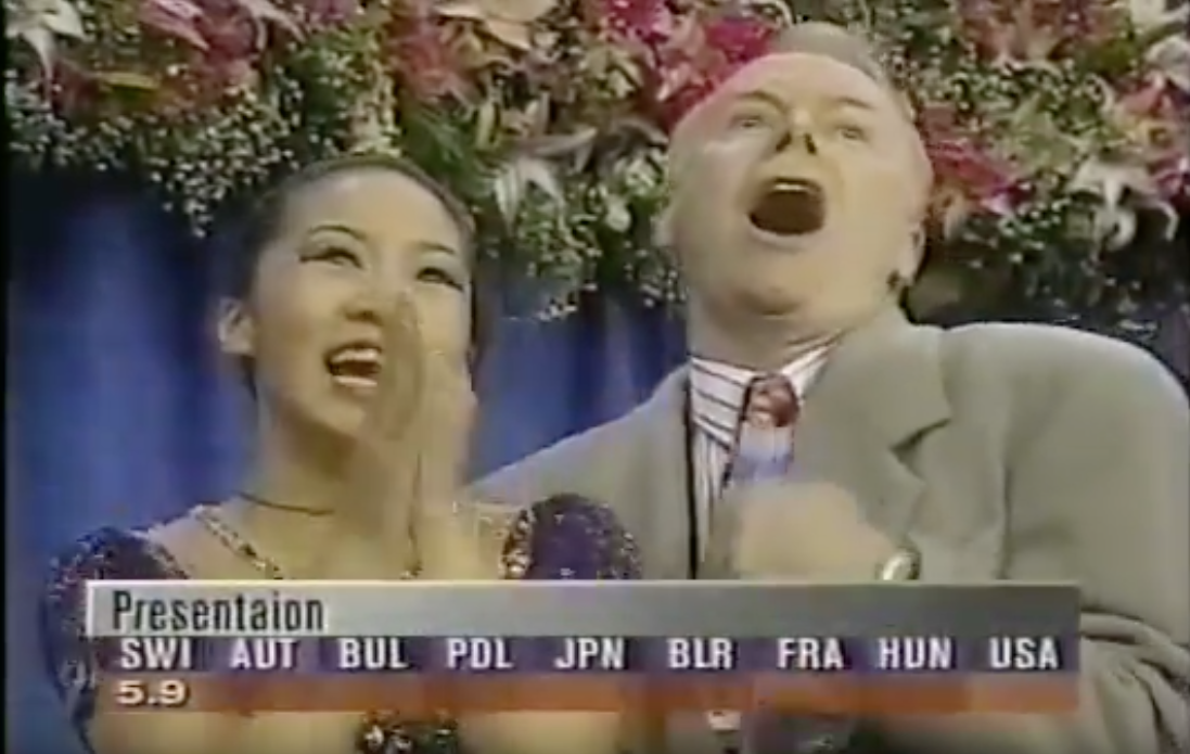 "Michelle Kwan and Frank Carroll exult as the free skate marks come up (two would be perfect 6.0s) at what the coach considers the standout performance of her career: ""Salome"" at the 1996 World Championships.  (Screenshot from ESPN)"