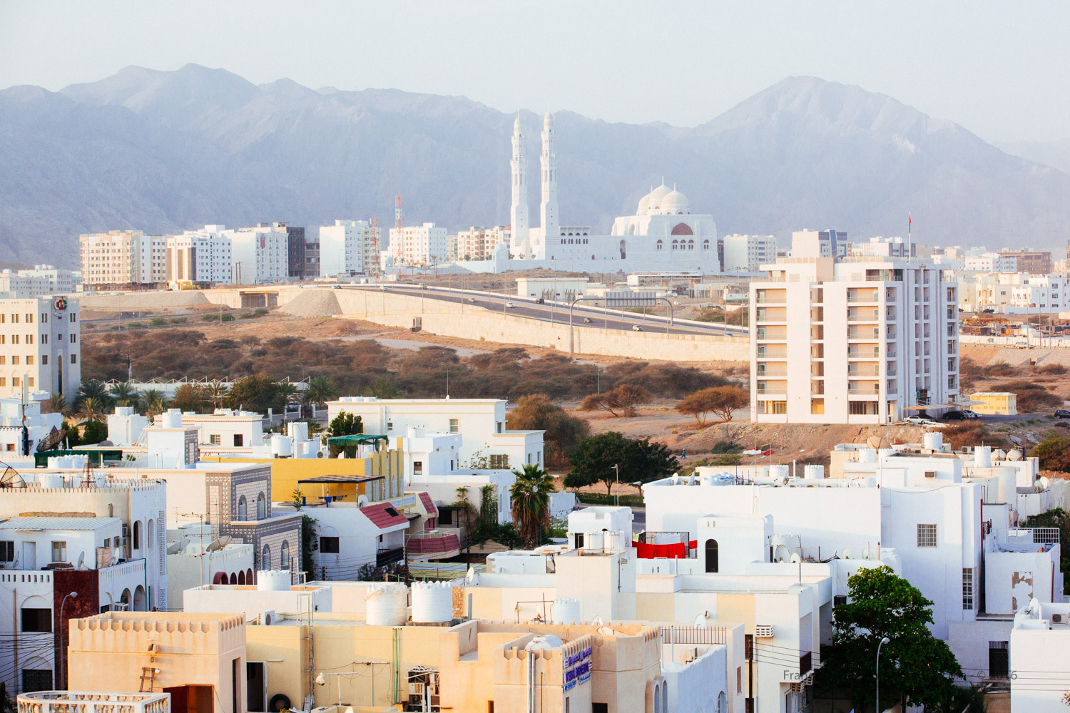 In the early morning, the mosque Saeed Bin Taimur Masjid seen from Ibis Hotel.In the background, the Western Al Hajar Mountains run through the northern coastline of the city.