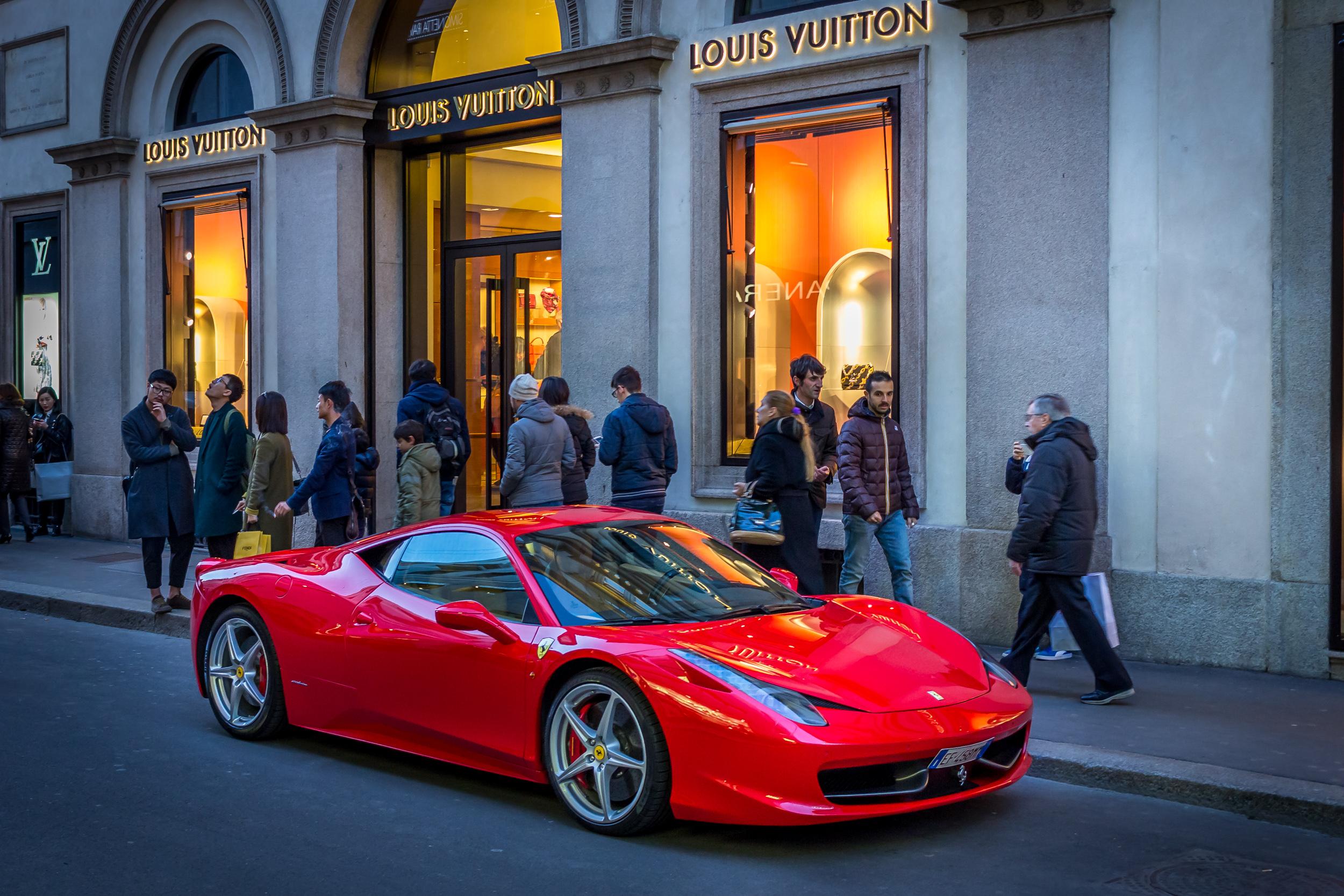A red Ferrari in front of Louis Vuitton on Via Montenapoleone. A classic cliché combination.