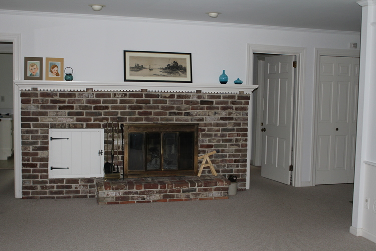 The fireplace sits between two bedroom hallways, and just beyond the main entrance hall