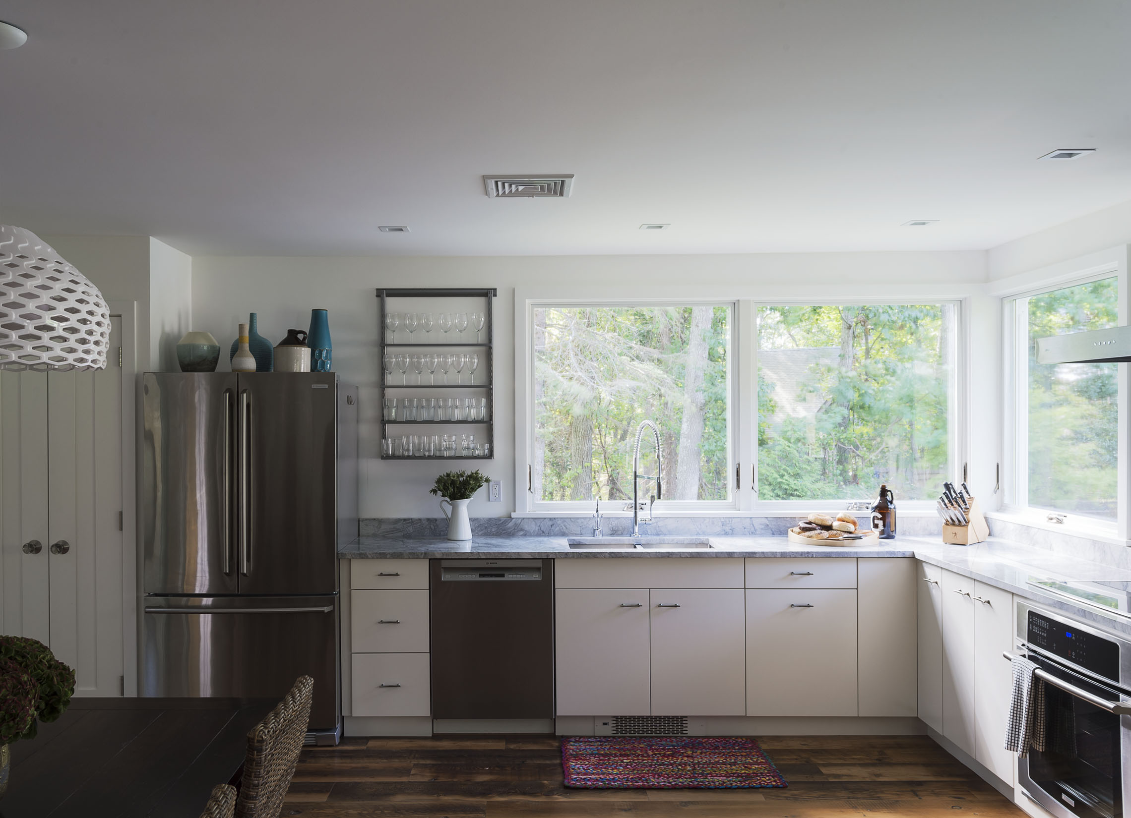A simple set of Elfa hanging trays provide glassware storage above the dishwasher in an otherwise empty wall of our North Fork home, via  tamarahubinsky.com