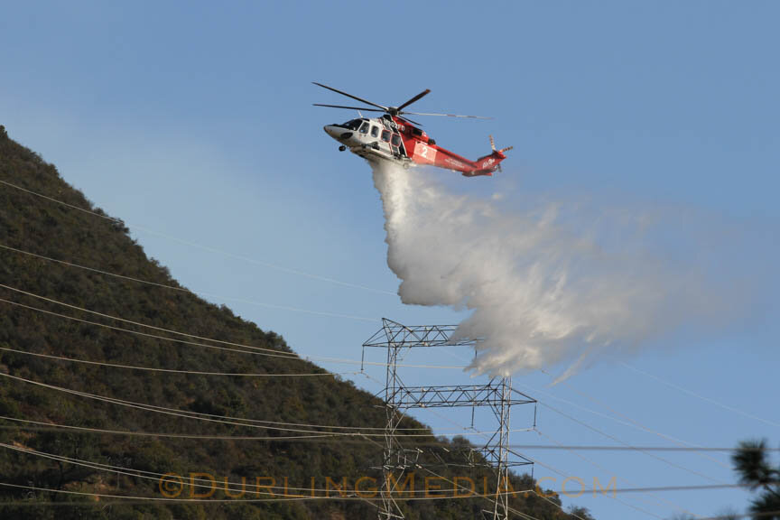 An LAFD helicopter makes a drop near power lines during the Barham Fire.