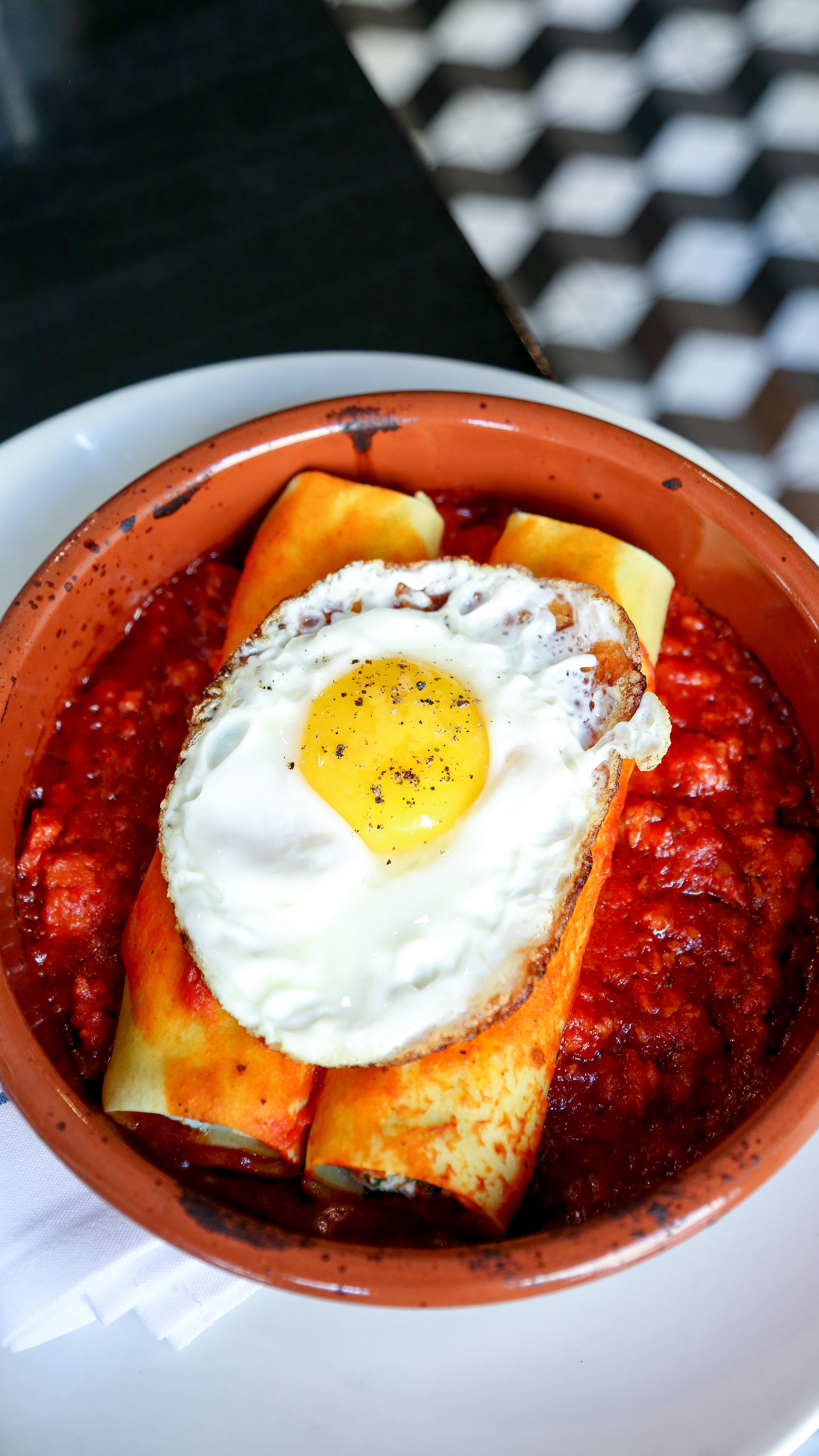 Cannelloni - spinach, ricotta, spicy italian sausage tomato sauce, olive oil fried egg