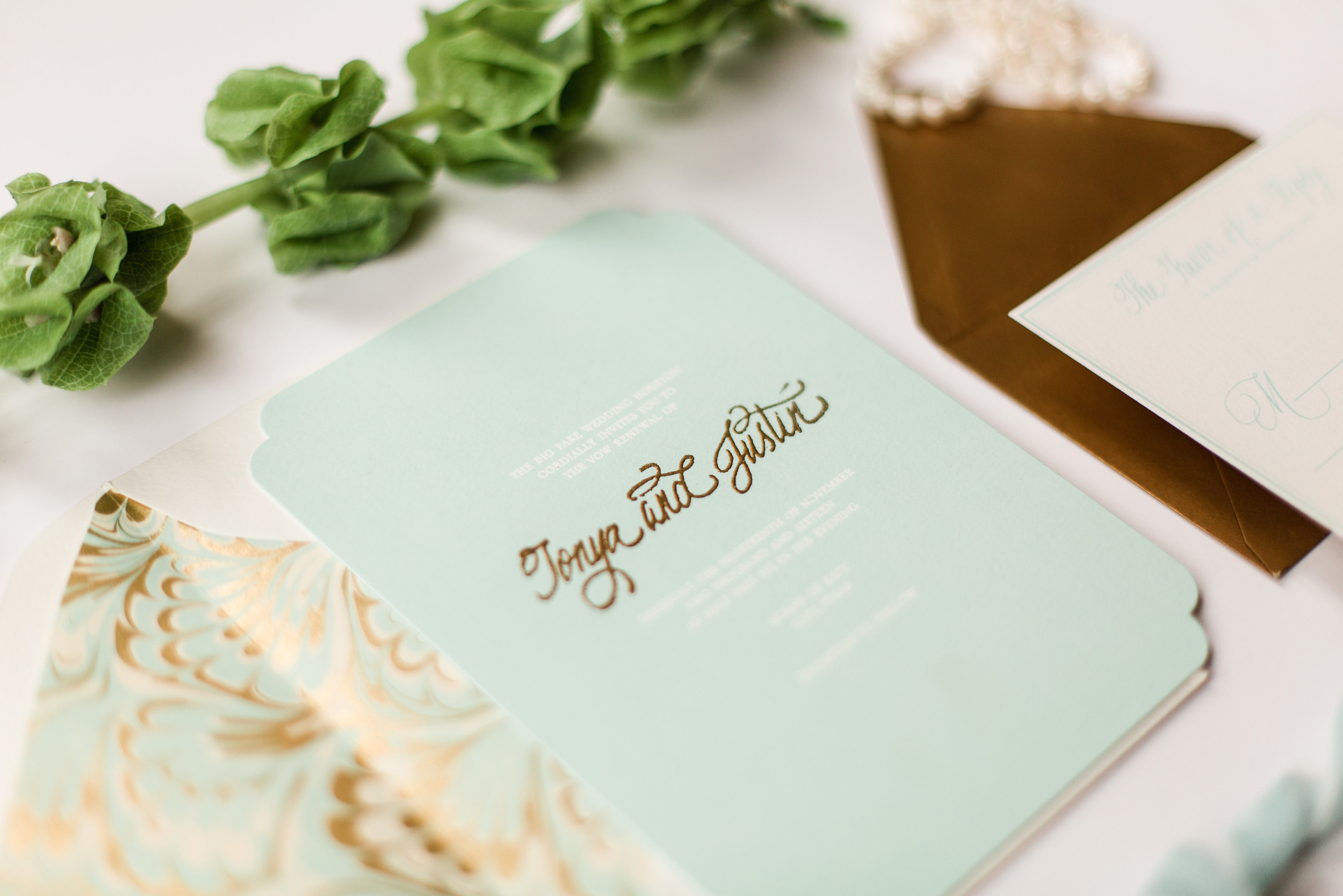 gold raised ink thermography wedding invitation with die cut edges on pale blue paper.jpg