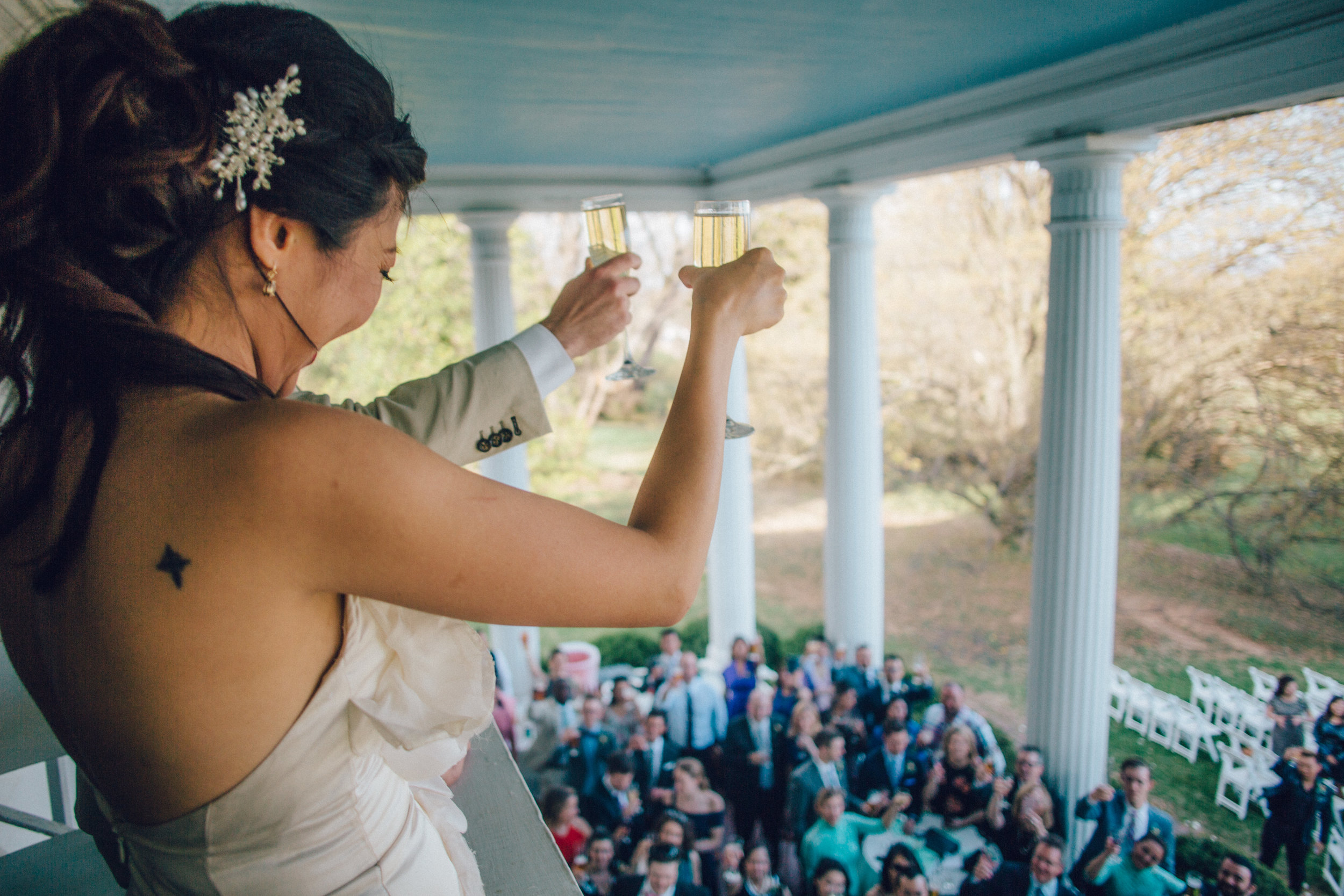 Les mariés saluent leurs invités de leur balcon.